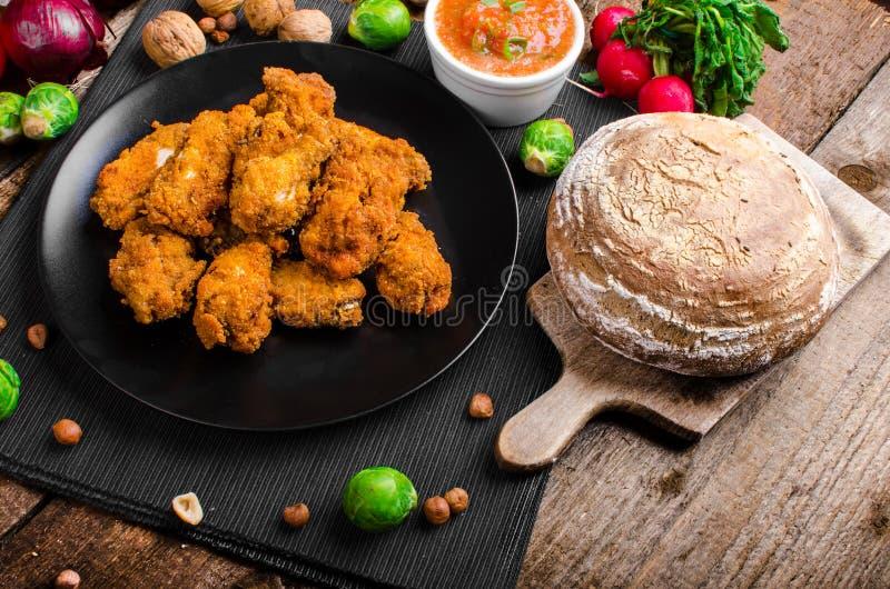 Korzenni breaded kurczaków skrzydła z domowej roboty chlebem fotografia stock