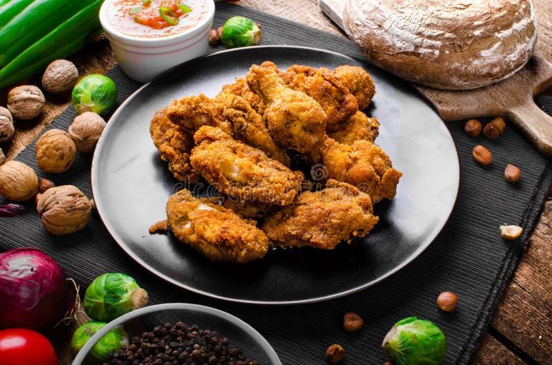 Korzenni breaded kurczaków skrzydła z domowej roboty chlebem obrazy stock
