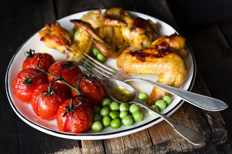 Korzenni kurczaków skrzydła, piec czereśniowi pomidory i zieleni grochy, Baslanced posiłek obraz royalty free