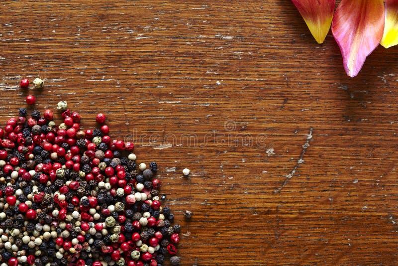 Korzenny pieprz i piękni kolorowi okwitnięcia na ciemnym drewnianym stole obrazy royalty free