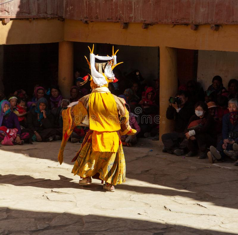Monk in deer mask with ritual sword performs religious mystery dance of Tantric Tibetan Buddhism on the Cham Dance Festival in Kor royalty free stock image