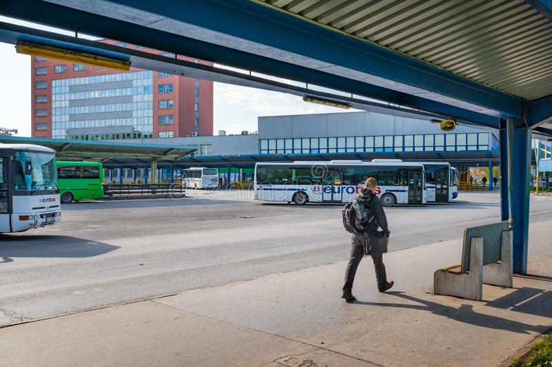 KOSICE, SLOVAKIA – MAY 1 2019: Yong man with backpack and laptop bag walks under platform shelter at Main bus station in Kosice. Slovakia stock image