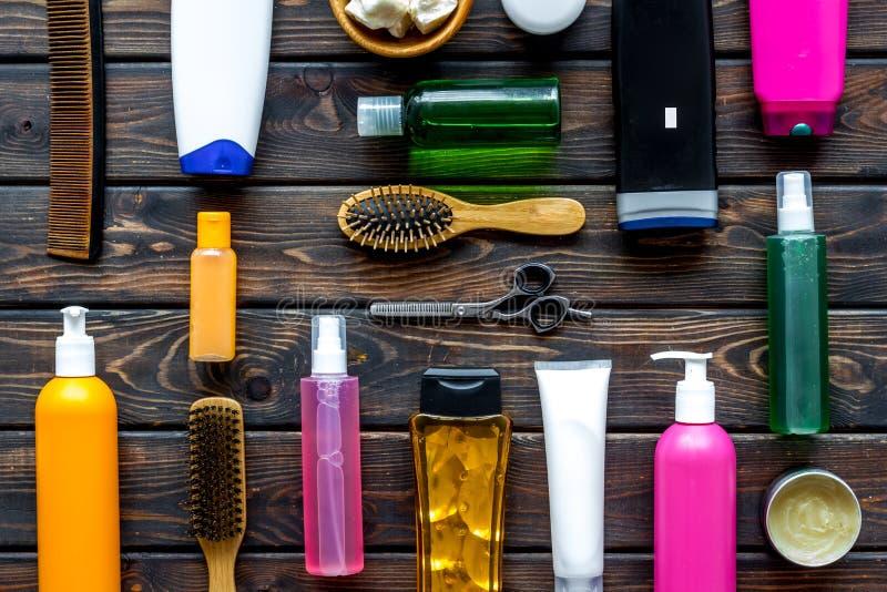 Kosmetik für Haar mit Öl, Scheren, Kamm, Conditioner und Shampoo in der Flasche auf hölzernem Draufsichtmuster des Hintergrundes stockbild