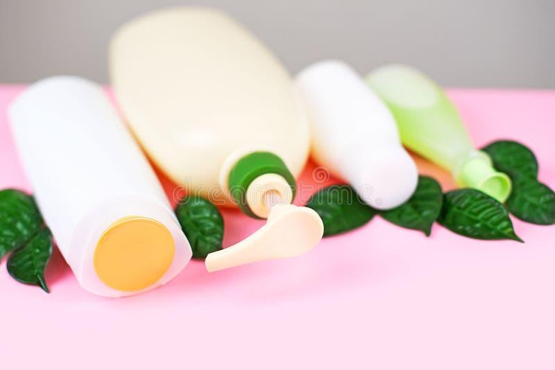 Kosmetik für Haar und weiße Flaschen der Körperpflege auf einem Kopienraum Bioprodukt des rosa Hintergrundes Natur, selektiver Fo stockfotos