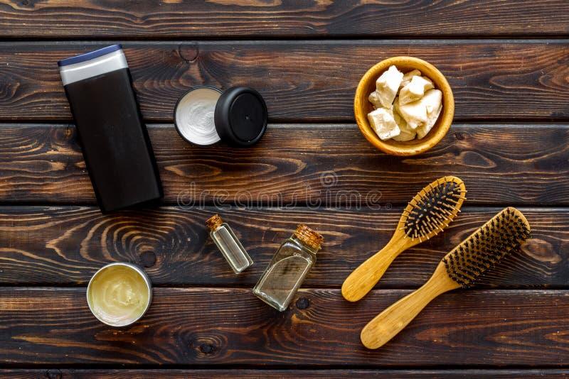 Kosmetik für Haarpflege mit Buxacee, Argan oder Kokosnussöl in der Flasche auf Draufsicht des hölzernen Hintergrundes lizenzfreies stockfoto