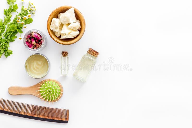Kosmetik für Haarpflege mit Buxacee, Argan oder Kokosnussöl in der Flasche auf weißem Draufsichtspott des Hintergrundes oben stockfoto