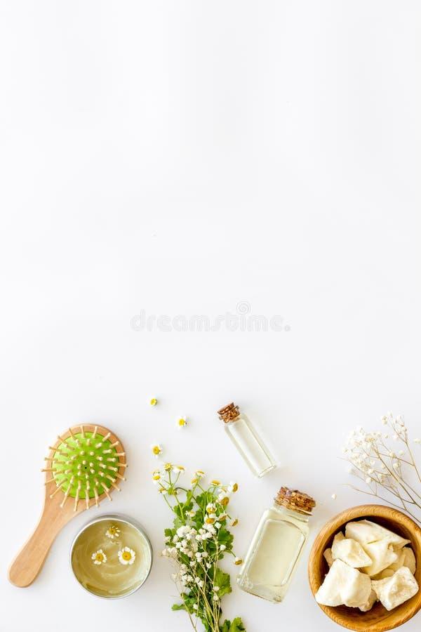 Kosmetik für Haarpflege mit Buxacee, Argan oder Kokosnussöl in der Flasche auf weißem Draufsichtspott des Hintergrundes oben lizenzfreie stockfotos
