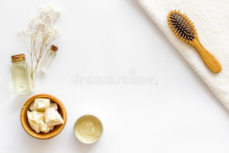Kosmetik für Haarpflege mit Buxacee, Argan oder Kokosnussöl in der Flasche auf weißem Draufsichtspott des Hintergrundes oben stockfotos