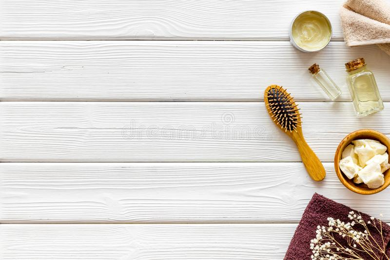 Kosmetik für Haarpflege mit Buxacee, Argan oder Kokosnussöl in der Flasche auf weißem hölzernem Draufsichtmodell des Hintergrunde lizenzfreie stockfotos