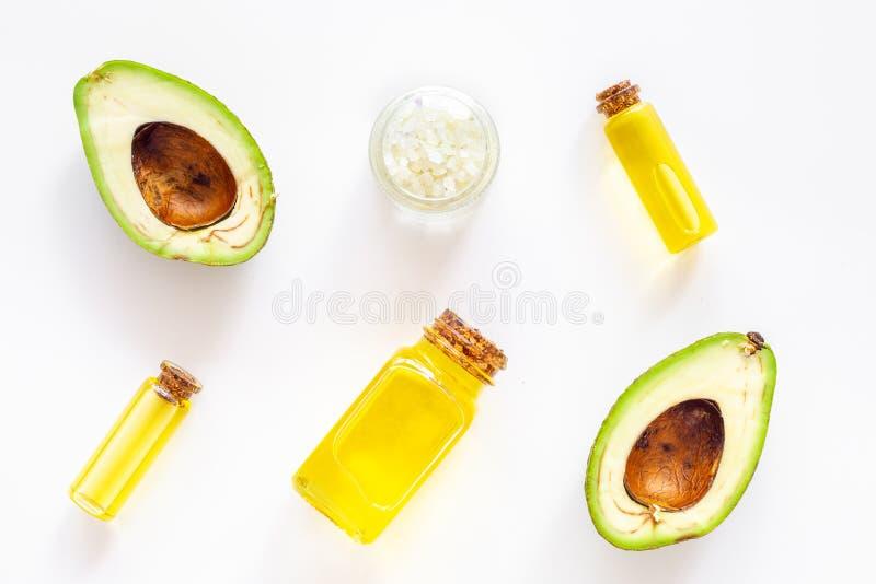Kosmetik für Hautpflege Avocadoöl nahe Hälfte der Avocado auf Draufsicht des weißen Hintergrundes lizenzfreie stockfotografie