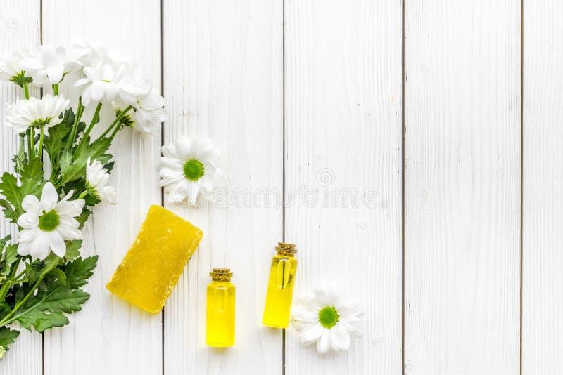 Kosmetik für Hautpflege mit Kamille Ölen Sie, seifen Sie auf weißem hölzernem Draufsicht-Kopienraum des Hintergrundes ein stockbild