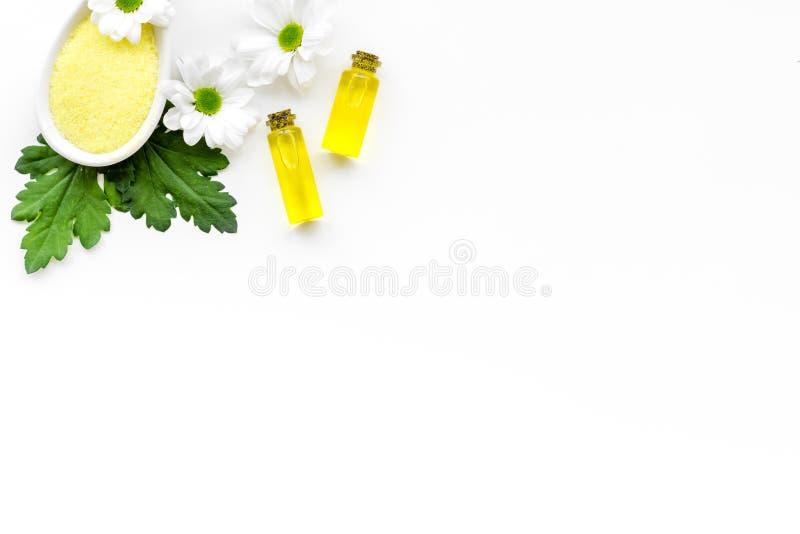 Kosmetik für Hautpflege mit Kamille Kamillenöl, Badekurortsalz auf weißem Draufsicht-Kopienraum des Hintergrundes stockfoto