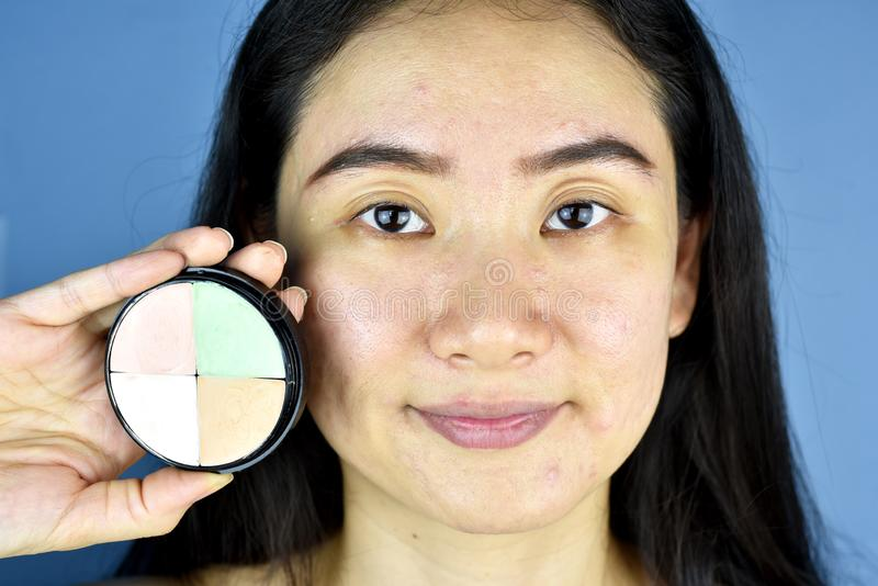 Kosmetik und Abdeckstift, Asiatin, die Farbkorrektur zeigt lizenzfreie stockfotos