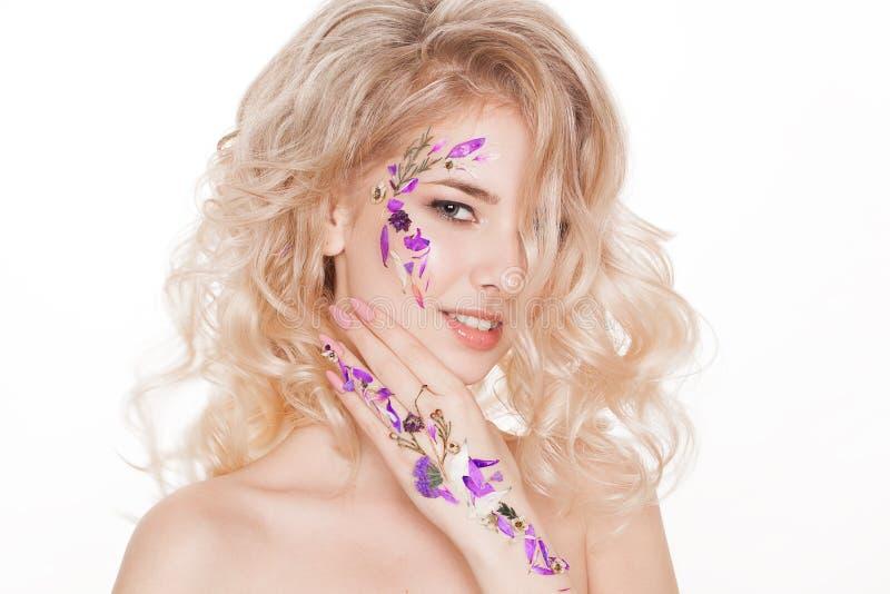 Kosmetik und Maniküre Nahaufnahmeporträt der attraktiven Frau mit trockenen Blumen auf ihrem Gesicht, Pastellfarbe des Nageldesig stockfoto