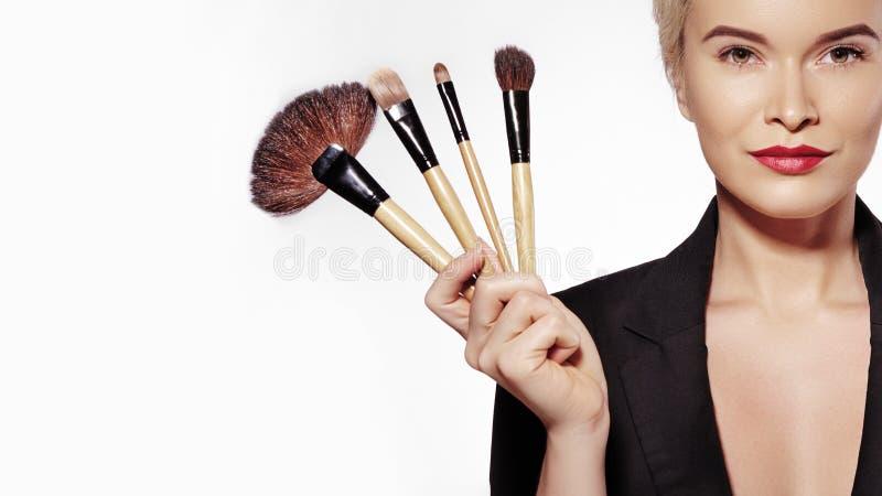 Kosmetik und Schönheits-Behandlung Schönes Mädchen mit Make-upbürsten umarbeitung Maskenbildner Applying Visage stockfotografie