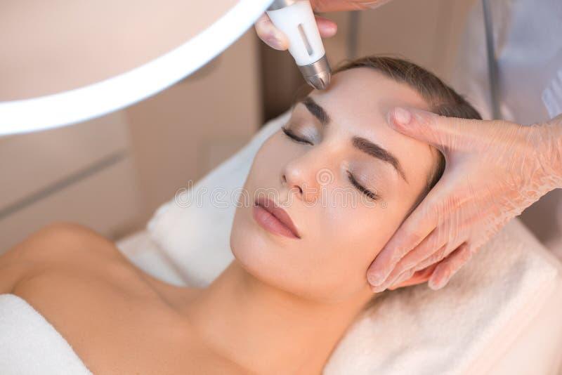 Kosmetiker, der Antialternverjüngungsverfahren auf Frauengesicht durchmacht lizenzfreies stockbild