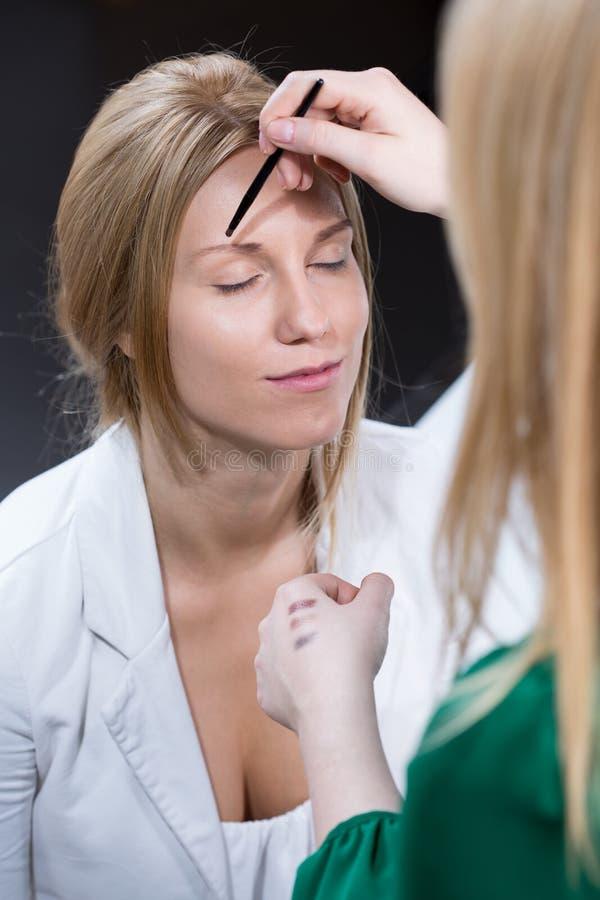 Kosmetiker, der Augenbraue bildet lizenzfreies stockfoto