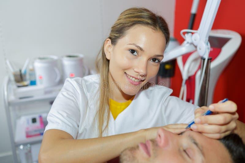 Kosmetiker, der dem männlichen Kunden Gesichtsumarbeitung gibt lizenzfreies stockfoto