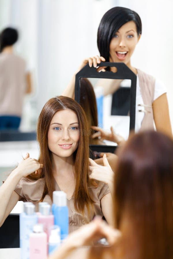 Kosmetiker, der den Haarschnitt des Kunden im Spiegel zeigt stockfotografie