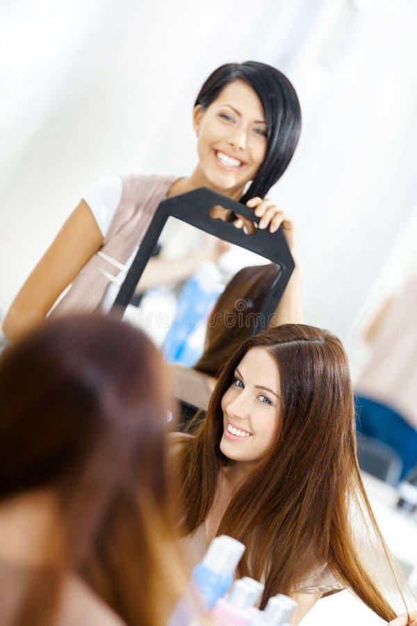 Kosmetiker, der die Frisur des Kunden im Spiegel zeigt lizenzfreie stockfotos