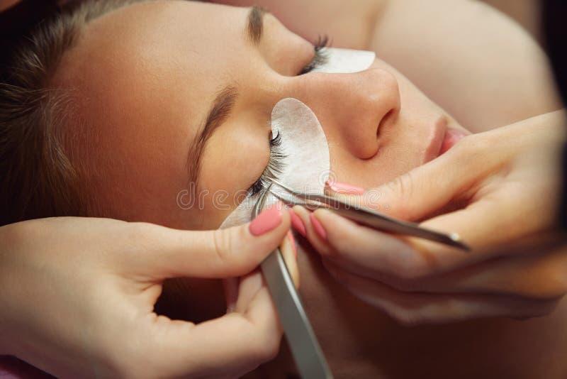 Kosmetiker, der k?nstliche Peitschen macht Wimper-Erweiterungs-Verfahren lizenzfreie stockfotos