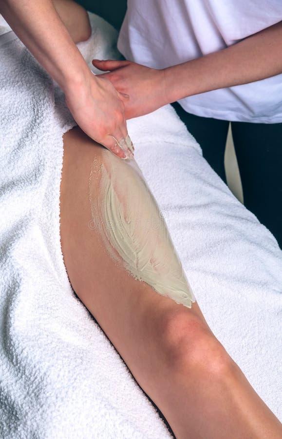 Kosmetiker, der Lehmbehandlung in den Frauenbeinen auf Badekurort anwendet stockfotografie