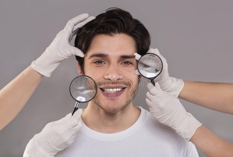 Kosmetiker, die junges Gesicht des gut aussehenden Mannes durch Vergrößerungsgläser überprüfen lizenzfreie stockfotos