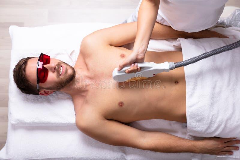 Kosmetiker-Giving Laser Epilations-Behandlung auf dem Kasten des Mannes stockbild