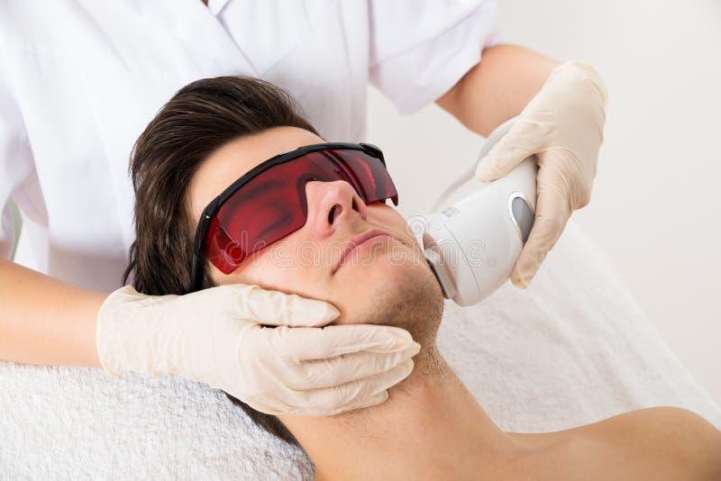 Kosmetiker-Giving Laser Epilations-Behandlung, zum des Gesichtes zu bemannen lizenzfreie stockfotografie