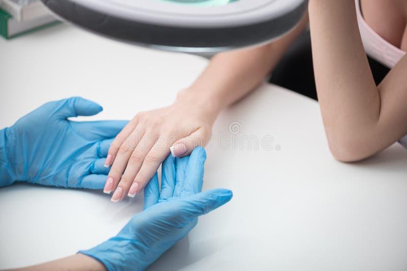 Kosmetiker ist Händchenhalten der jungen Frau lizenzfreie stockfotos