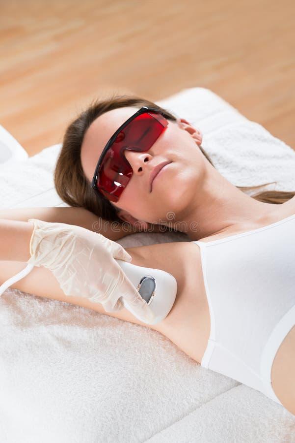 Kosmetiker-Removing Hair Of-Frau mit Epilator stockfotos