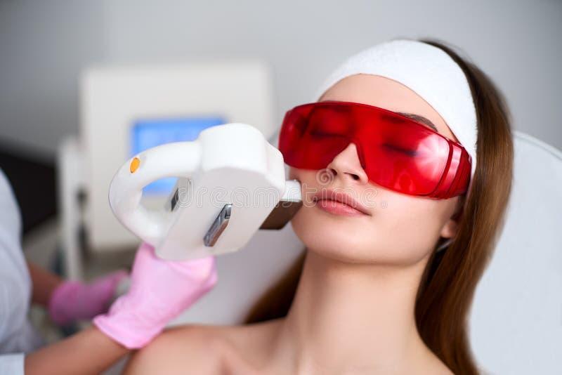 Kosmetikerdoktor, der Laser Rf-Verj?ngung f?r h?bsches Gesicht der jungen Frau am Sch?nheitssalon tut Elos-epilation Haarabbau stockbild