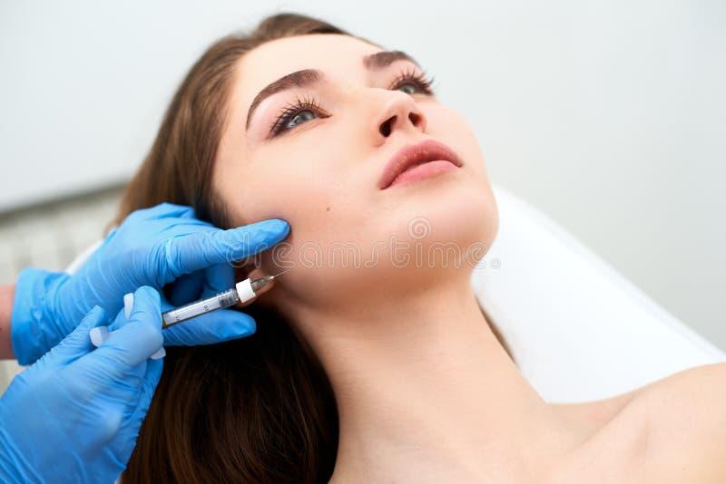 Kosmetikerdoktor mit der Füllerspritze, die Einspritzung zu den Wangen macht Masseter-Linien Reduzierung und umreißende Therapie  stockbilder