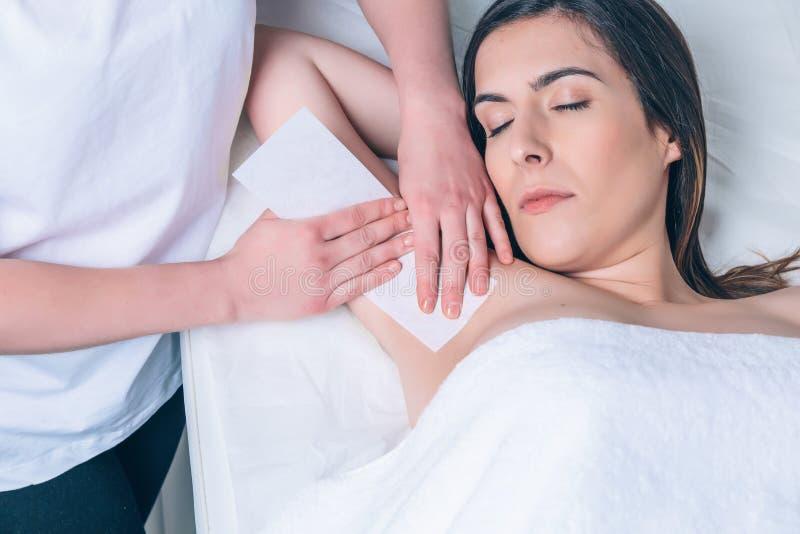 Kosmetikerhände, die Enthaarung in der Frauenachselhöhle tun lizenzfreie stockbilder
