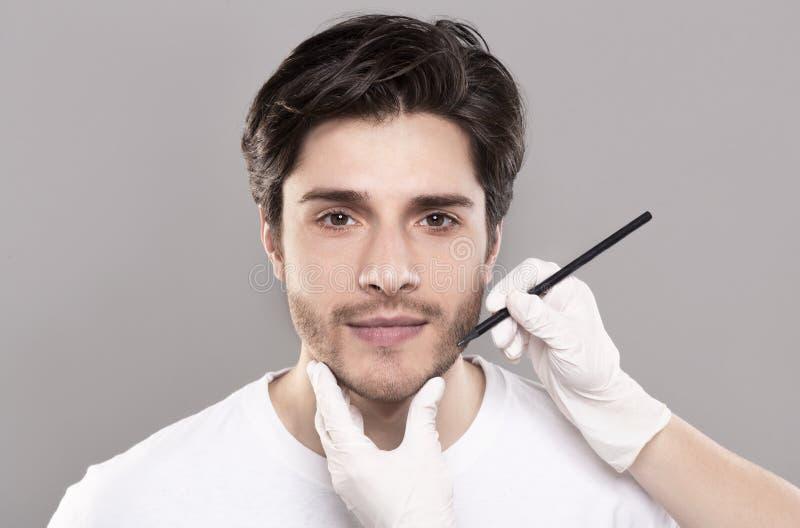 Kosmetikerhände, die männliches Gesicht vor Schönheitsoperation markieren lizenzfreie stockbilder