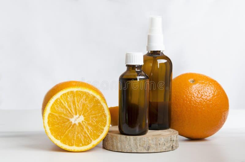 Kosmetikflaschen und frische Orangen, hölzernes Brett gegen weiße Wand Konzept von Badekuren lizenzfreie stockfotos
