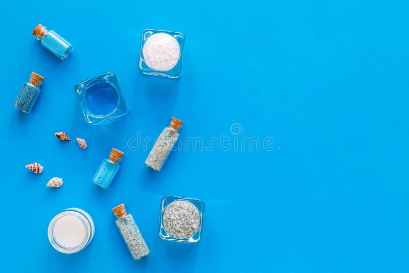 Kosmetikplan des Toten Meers Seesalz in den Flaschen und in den Schüsseln nahe kleinen Oberteilen auf blauem Draufsicht-Kopienrau lizenzfreies stockbild