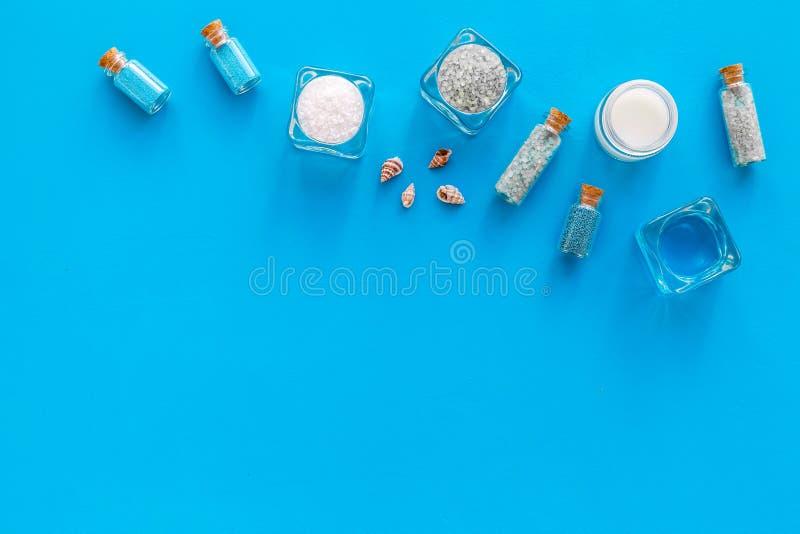 Kosmetikplan des Toten Meers Seesalz in den Flaschen und in den Schüsseln nahe kleinen Oberteilen auf blauem Draufsicht-Kopienrau lizenzfreie stockbilder