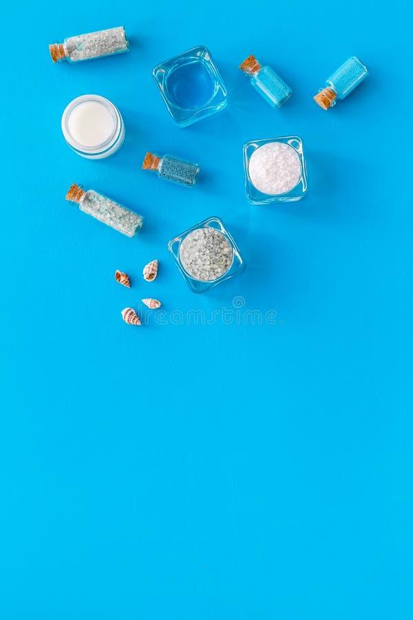 Kosmetikplan des Toten Meers Seesalz in den Flaschen und in den Schüsseln nahe kleinen Oberteilen auf blauem Draufsichtraum des H stockbild