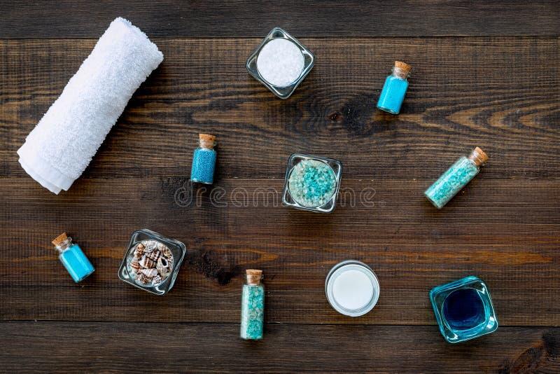 Kosmetikplan des Toten Meers Seesalz in den Flaschen und in den Schüsseln nahe kleinen Oberteilen auf Draufsicht des dunklen hölz lizenzfreie stockbilder