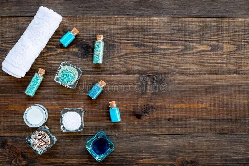 Kosmetikplan des Toten Meers Seesalz in den Flaschen und in den Schüsseln nahe kleinen Oberteilen auf dunklem hölzernem Draufsich lizenzfreie stockfotos