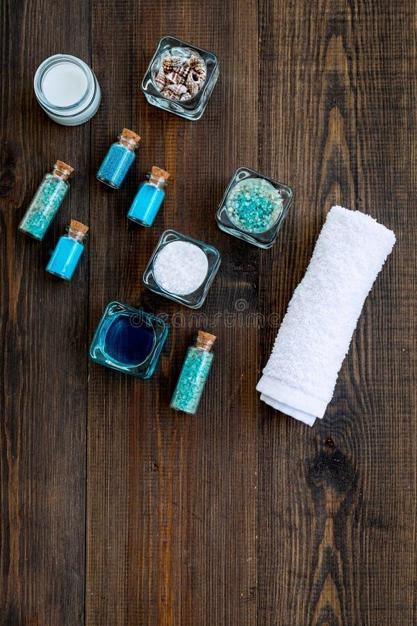 Kosmetikplan des Toten Meers Seesalz in den Flaschen und in den Schüsseln nahe kleinen Oberteilen auf dunklem hölzernem Draufsich stockbild