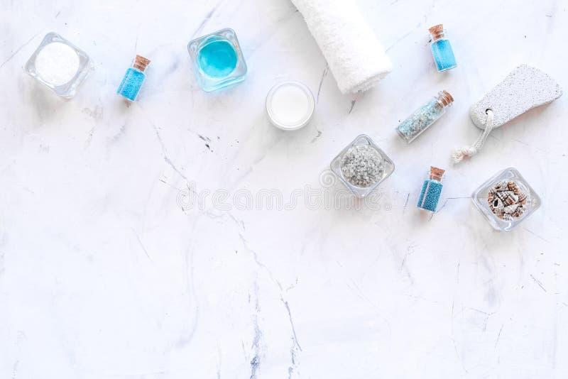 Kosmetikplan des Toten Meers Seesalz in den Flaschen und in den Schüsseln nahe kleinen Oberteilen und Tuch auf Draufsicht des wei lizenzfreie stockfotografie