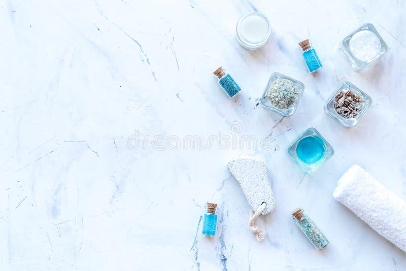 Kosmetikplan des Toten Meers Seesalz in den Flaschen und in den Schüsseln nahe kleinen Oberteilen und Tuch auf Draufsicht des wei lizenzfreie stockbilder