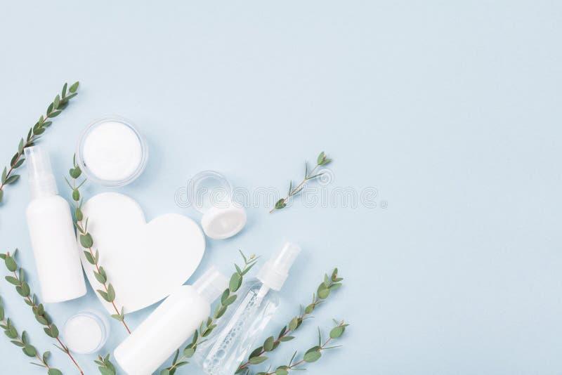 Kosmetiksatz für Hautpflege- und Schönheitsbehandlung verziert mit weißer hölzerner Draufsicht der Herz- und Eukalyptusblätter Fl lizenzfreies stockfoto