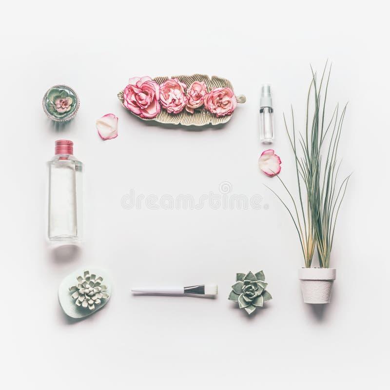 Kosmetisch plaatsend kader voor gezichtshuidzorg met roze rozen en rozenwater of toner op witte achtergrond royalty-vrije stock fotografie