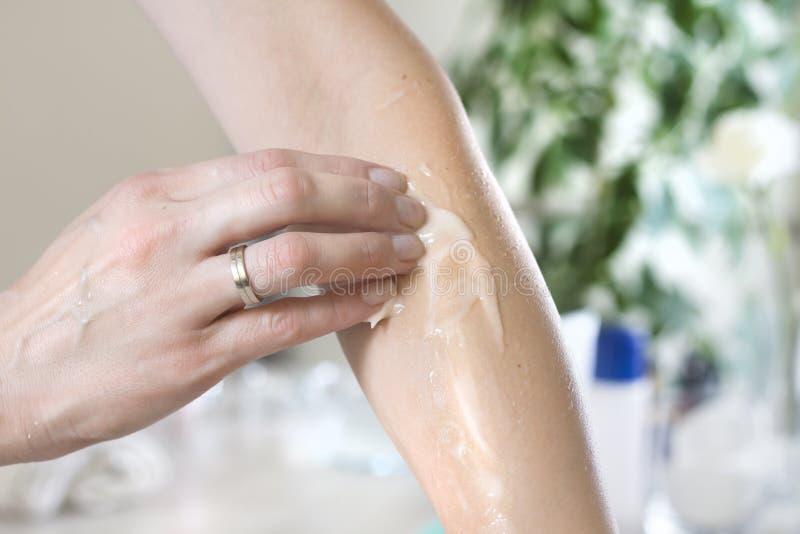 Kosmetische behandeling De hand van een vrouw zet een balsem op haar voorarm royalty-vrije stock fotografie