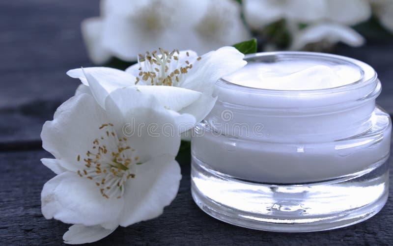 Kosmetische Creme in einem Glasgefäß mit Jasminblumen auf einem hölzernen Hintergrund lizenzfreie stockfotos