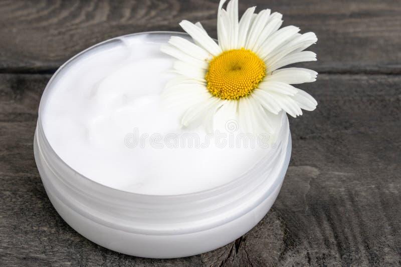 Kosmetische Creme nahe Kamillenblumen auf einem Holztisch lizenzfreie stockfotografie