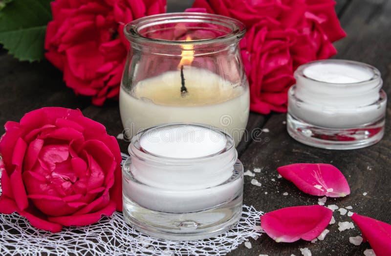 Kosmetische Creme und Rosen mit den Blumenblättern und einer brennenden Kerze auf dem alten hölzernen Hintergrund lizenzfreie stockfotos